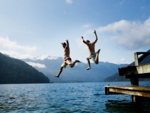 Two male friends jumping off dock into lake in mid air